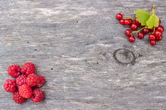 Juicy raspberries and red currants lying on wooden table with leaves. Juicy raspberries and red currants lying on an old wooden table with three green leaves Stock Photography