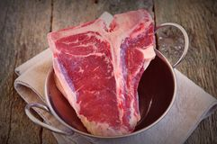 Juicy raw beef t-bone steak on wooden table.selective focus.image is tinted Stock Photos