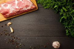 Juicy raw meat with spices, pepper, sea salt and herbs. Lies on a dark wooden background stock image