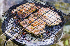 Juicy raw steaks on the grill. Delicious roasted steaks on the grill -outdoor barbecue Royalty Free Stock Photography