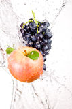 Juicy red apple and bunch of grapes in water Stock Photos