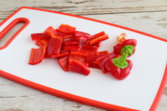 Juicy red bell pepper cut up on white cutting board. step by step cooking. Stock Photography
