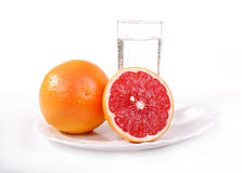 Juicy red grapefruit. And a glass of mineral water on a white background Stock Images