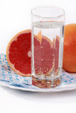 Juicy red grapefruit. And a glass of mineral water on a white background Stock Photos