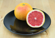 Juicy red grapefruit on the black plate. Stock Photos