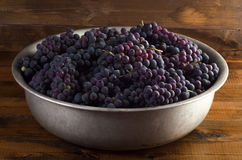 Juicy red grapes in bowl on wooden background. Juicy red grapes in bowl on a wooden background Stock Photography