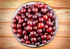 Juicy red grapes in bowl on wooden background. Detailed studio shot Royalty Free Stock Images
