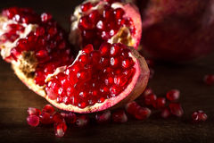 Juicy red pomegranate with seeds on wooden table Stock Image