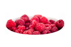 Juicy red raspberries in the white bowl isolated Stock Images