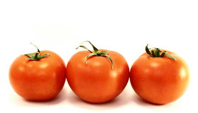 Juicy red ripe tomatoes. On a white background royalty free stock image