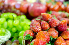 Juicy red strawberries with grapes in the background. Juicy red strawberries closeup with grapes in the background Royalty Free Stock Image
