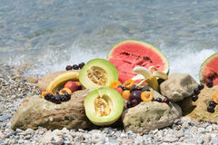 Juicy and refreshing summer fruits on the rocks against the blue sea. Stock Photography