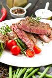 Juicy rib-eye steak with potato wedges and french beans. stock image