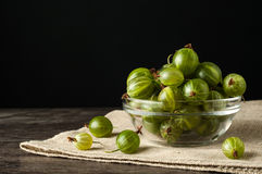 Juicy ripe berries of a gooseberry in a small glass plate on black surface. Gooseberry harvest Stock Images