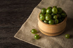 Juicy ripe berries of a gooseberry in a small wooden pot on black surface. Gooseberry harvest Stock Photo