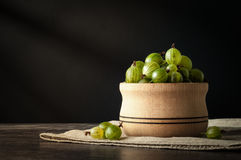 Juicy ripe berries of a gooseberry in a small wooden pot on black surface. Gooseberry harvest Stock Images