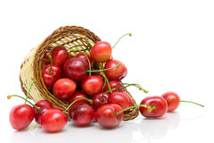 Ripe cherry in a wicker basket on a white background close-up. Royalty Free Stock Photos