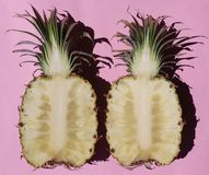 Pineapple Halves Open on Pale Pink Background. Juicy ripe fresh tropical healthy pineapple halves on Pink Background.Fruit royalty free stock image