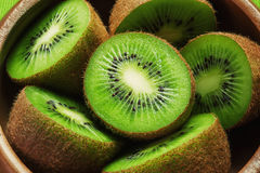Juicy ripe kiwi fruit on wooden plate. Juicy ripe green kiwi fruit Royalty Free Stock Images