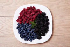 Juicy ripe natural organic raspberries blueberries blackberries. Beautiful juicy ripe natural organic raspberries, blackberries, blueberries lie on a white plate Stock Image