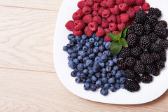Juicy ripe natural organic raspberries blueberries blackberries. Beautiful juicy ripe natural organic raspberries, blackberries, blueberries lie on a white plate Royalty Free Stock Photo