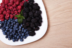 Juicy ripe natural organic raspberries blueberries blackberries. Beautiful juicy ripe natural organic raspberries, blackberries, blueberries lie on a white plate Stock Photo