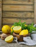 Juicy and ripe organic lemons in a and fresh mint on a wooden background Royalty Free Stock Photo