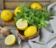 Juicy and ripe organic lemons in a and fresh mint on a wooden background Stock Photos