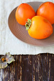 Juicy ripe persimmon on a plate Royalty Free Stock Photography