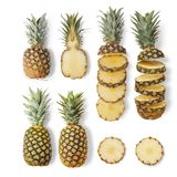 Juicy ripe pineapples of different varieties are whole and cut on a white background. From top view royalty free stock images