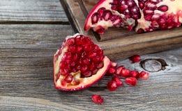 Juicy ripe pomegranates on vintage wood Royalty Free Stock Image