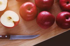 Juicy ripe red apples on wooden Board on black background. Cut the Apple in half. Next to the knife with a wooden handle. Proper stock images