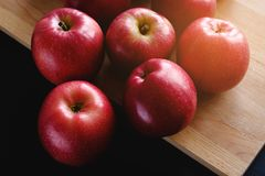 Juicy ripe red apples on wooden Board on black background. Proper diet. Healthy diet. Vegetarianism. Veganism. Live food. A Real royalty free stock image
