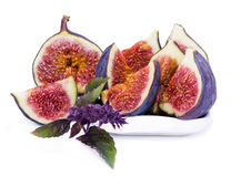 Juicy, ripe slices of fig and basil flower. Some juicy, ripe slices of fig and basil flower on white background stock photo