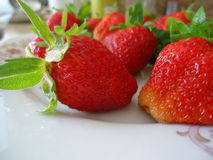 Juicy ripe strawberries with leaves on a plate, mouthwatering berry Stock Photo