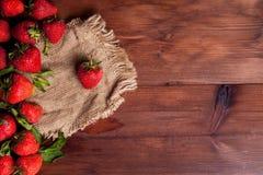 Juicy ripe strawberry. On wood tableon linen napkin Stock Image