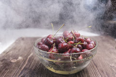 A juicy ripe sweet cherry lies in a transparent bowl under small drops of water droplets and a cold steam Royalty Free Stock Photography