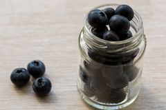 Juicy ripe tasty blueberries are in the glass jar stock images