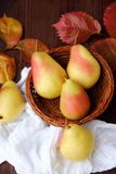 Juicy ripe yellow pears and autumn leaves in a wooden table Royalty Free Stock Photography