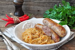 Juicy Roasted Bavarian sausages with the stewed cabbage Royalty Free Stock Photos
