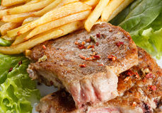Juicy roasted pork steak with french fries and spices Stock Image