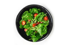 Juicy salad with spinach and tomatoes. Juicy fresh salad with spinach and tomatoes, flavored with olive oil, located on a black plate stock photos
