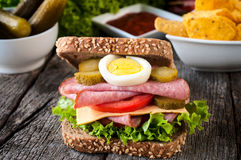 Juicy sandwich. Big toast sandwich with sausage on the wooden table Royalty Free Stock Image
