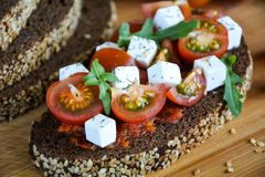 Juicy sandwich with tomato, cheese and herbs on black bread with cereals stock photos