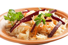 Juicy sauerkraut with beets and greens. On the plate.   Isolated on white Stock Photos