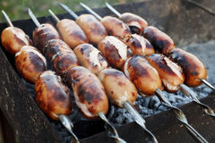 Juicy sausages grilled over charcoal Stock Photos