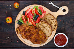 Juicy schnitzel with ciabatta, tomato salad on a dark wooden background. royalty free stock photography