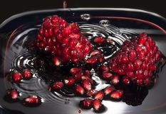 Juicy seeds of pomegranate in own juice. Close up against a dark background stock photography
