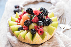 Juicy sliced melon stuffed with berry fruit Stock Image