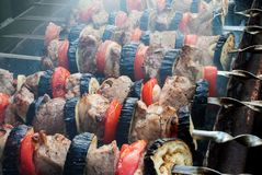 Juicy slices of meat with sauce prepare on fire shish kebab.  royalty free stock image